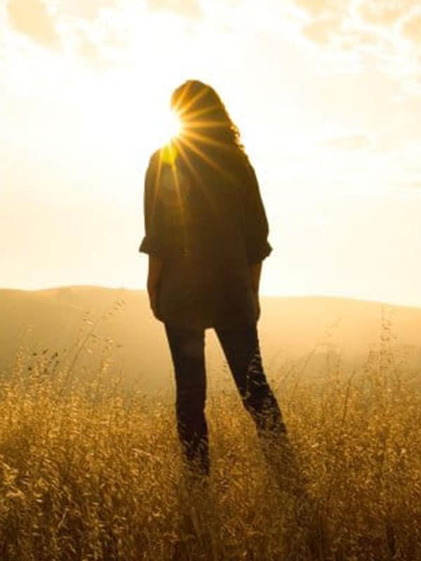 Living life to the fullest - woman standing in field at sunset