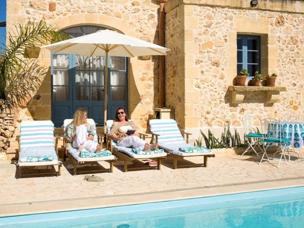 Guests relax at the pool at L'Gharix yoga and meditation retreat, Gozo