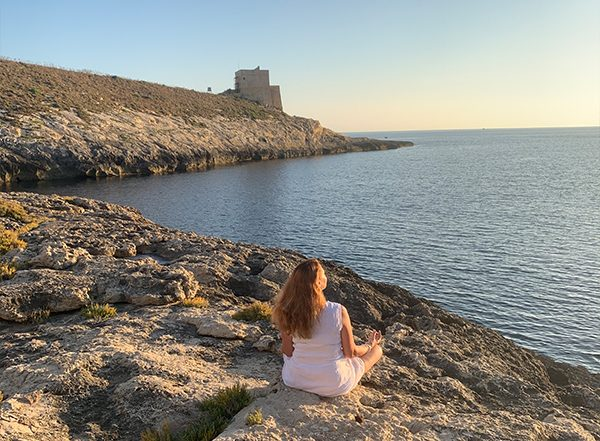 Karin Laing self-hypnosis meditating at Xlendi beach, Gozo, Malta